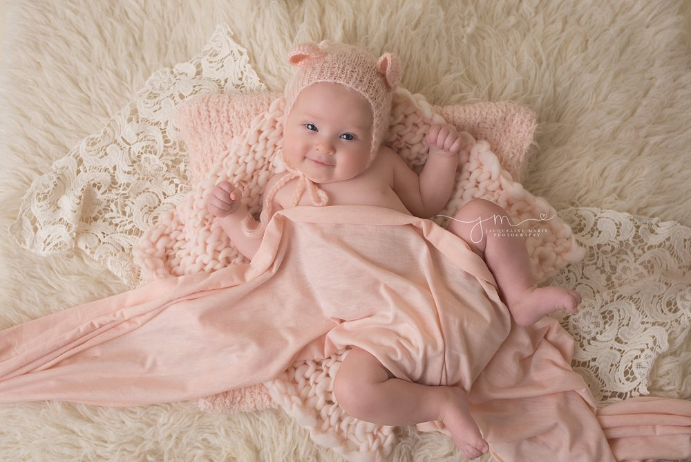 Columbus Ohio baby wears pink bonnet and is covered in pink wrap for milestone photography session at Jacqueline Marie Photography