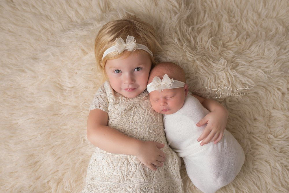 Columbus Ohio newborn portrait features big sister hodling newborn baby at Jacqueline Marie Photography studio