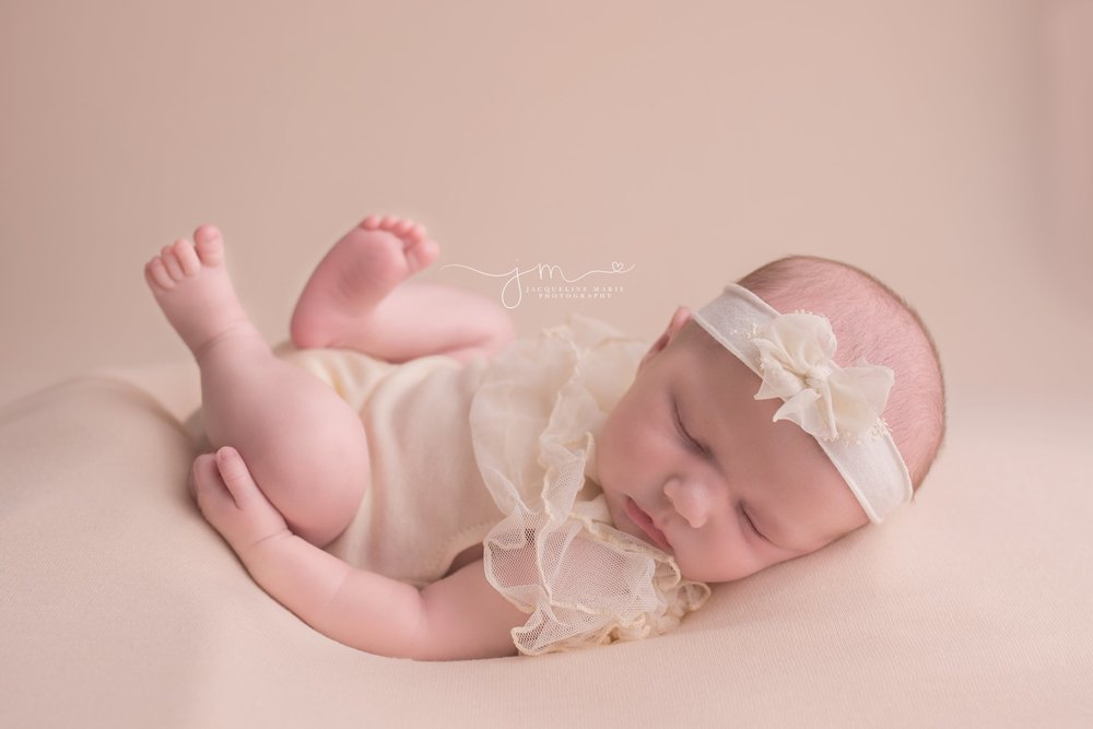 17 day old newborn wears cream lace romper and matching headband for portrait at Jacqueline Marie Photography in Columbus Ohio