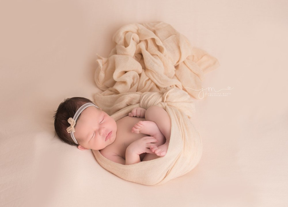 newborn photography by jacqueline marie photography features baby girl wrapped in blush pink layer