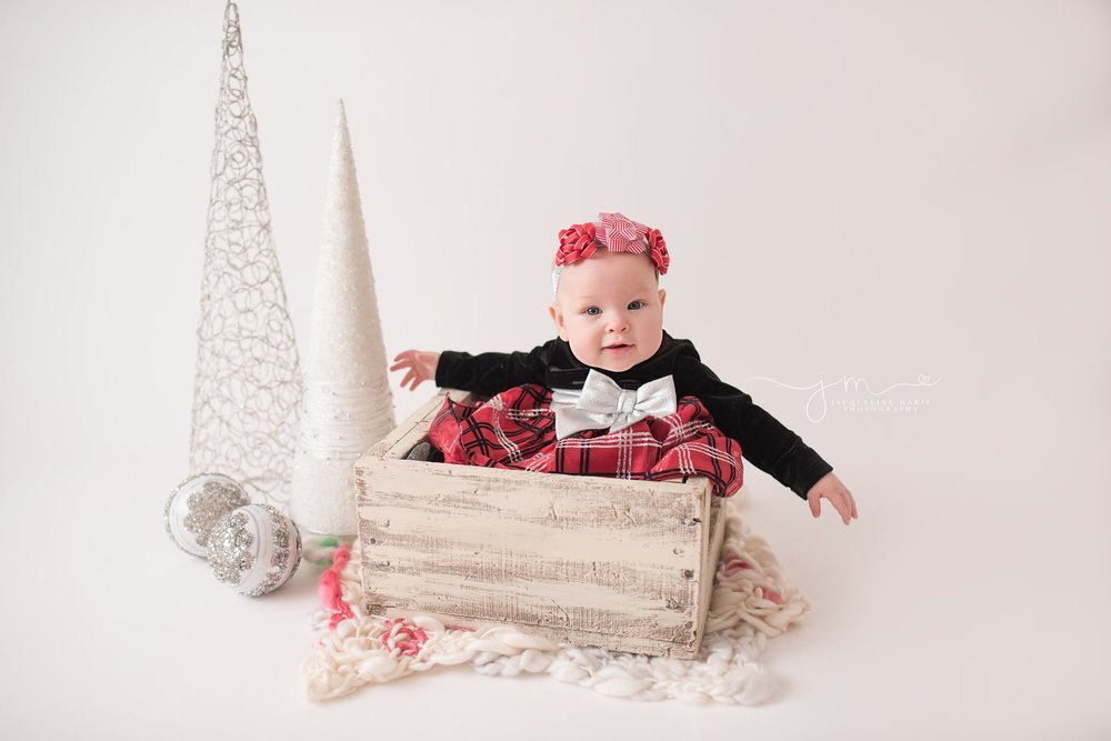 6 month baby girl wears Christmas dress in Columbus Ohio for portrait at Jacqueline Marie Photography studio