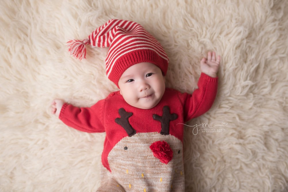 3 month old baby girl wears reindeer sweater outfit with santa hat for photography session at Jacqueline Marie Photography in Columbus Ohio