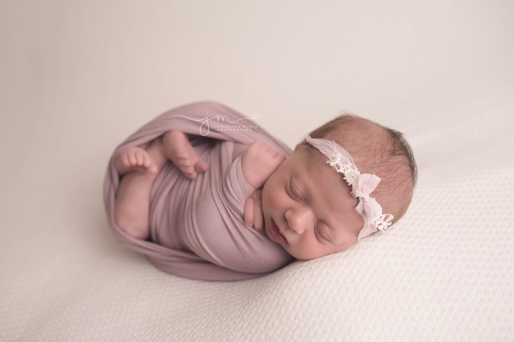 Jacqueline Marie Photography studio features newborn baby girl swaddled in purple wrap with matching headband for newborn photography session in Columbus Ohio