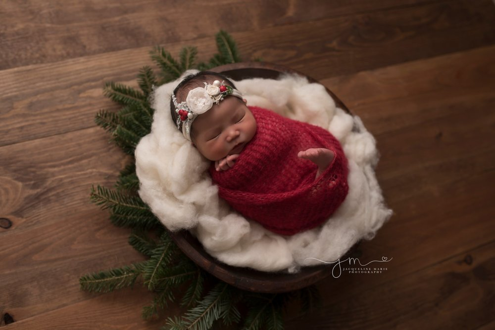 Newborn baby girl portrait features baby with red knit wrap and matching headband to symbolize the Chinese culture in Columbus Ohio