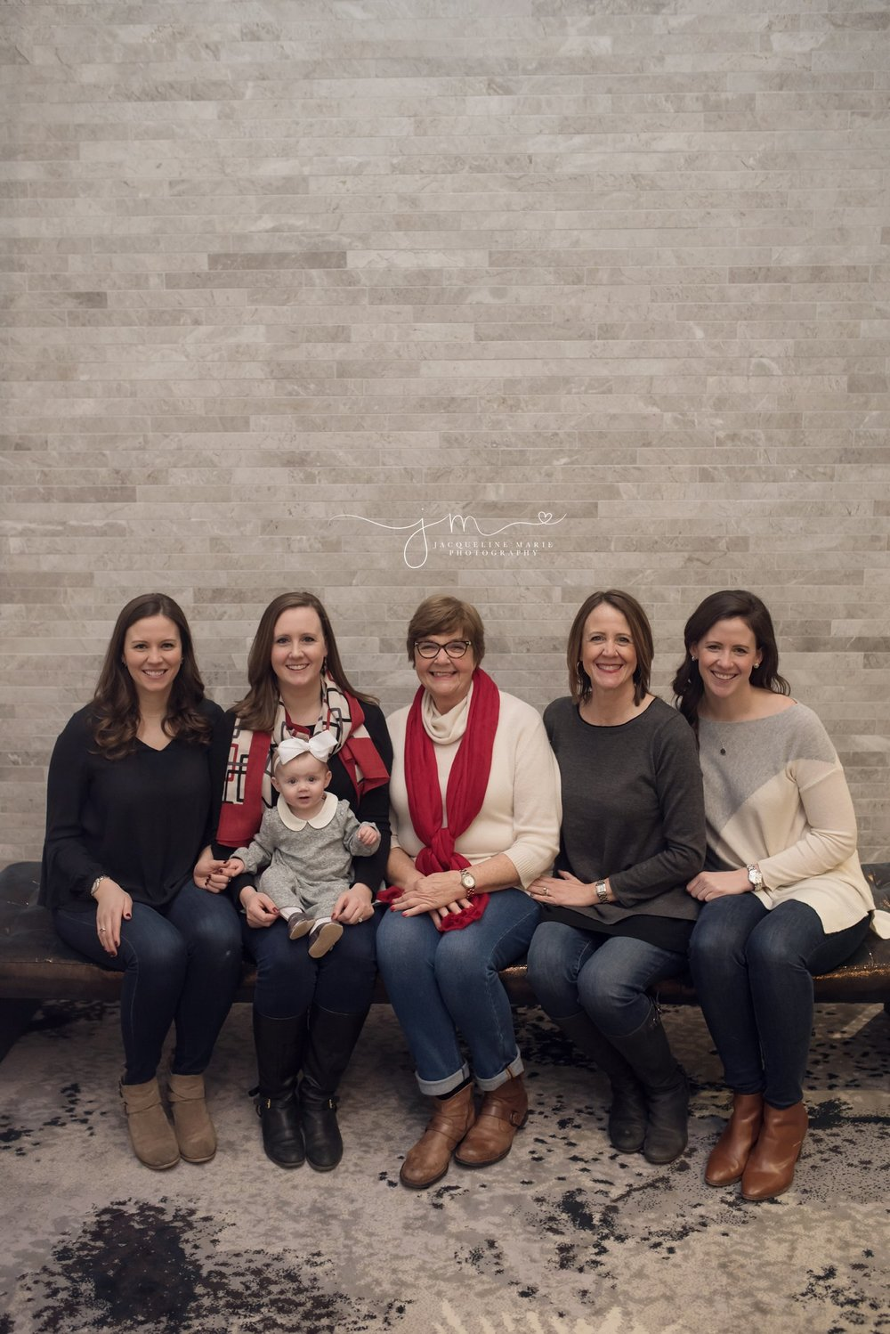 Granddaughters sit with great grandmother wearing jeans and sweaters inside Hilton Hotel in Columbus Ohio for family portraits