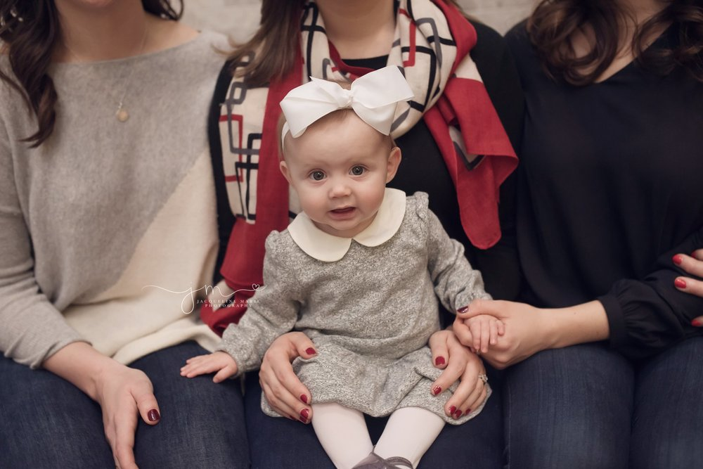 6 month old baby girl wears gray dress and white bow for family pictures at the Hilton Hotel in Columbus Ohio