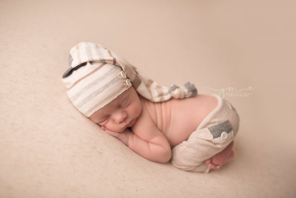 columbus ohio newborn image features baby boy posed in pants and matching hat for newborn portraits
