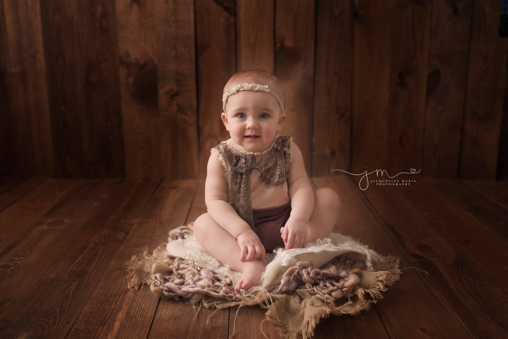 first birthday photographer features baby girl sitting in wood bowl for first birthday pictures in columbus ohio