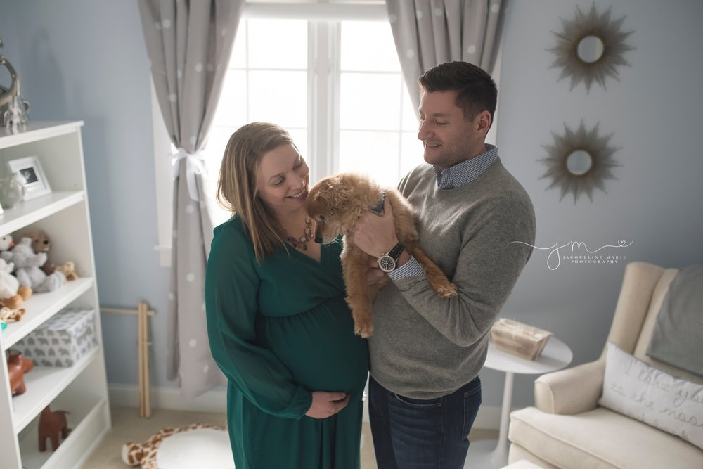 columbus ohio newborn photographer features portrait of expecting parents holding dog in nursery