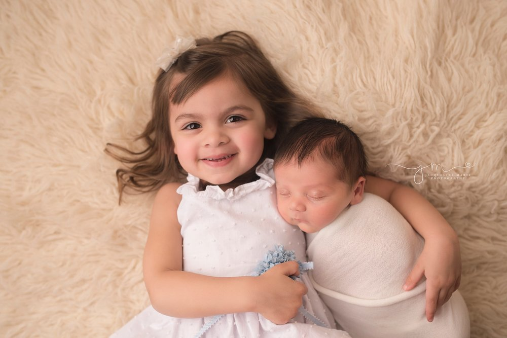columbus ohio newborn photographer features big sister holding baby brother for newborn pictures by jacqueline marie photography