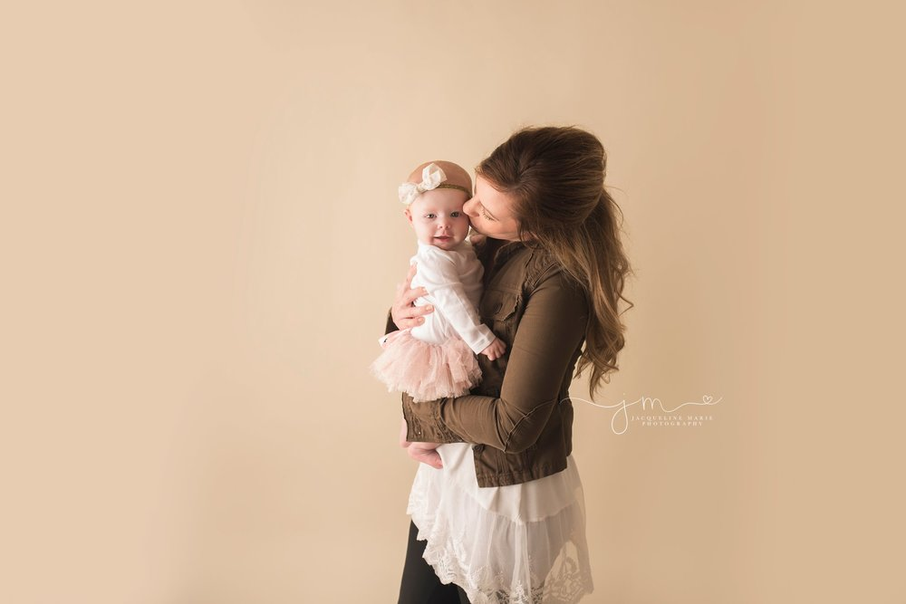 mother holds baby girl and kisses her cheek in columbus ohio for baby photography by jacqueline marie photography
