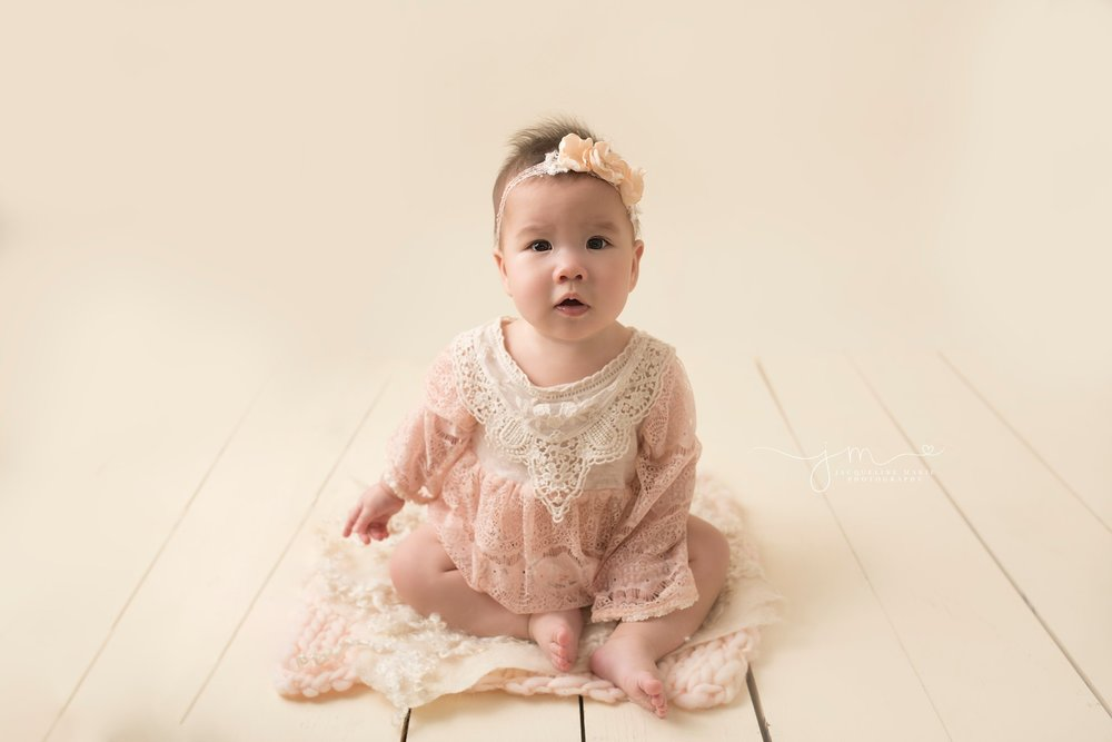 columbus ohio baby photographer features 6 month baby girl wearing lace romper and matching headband