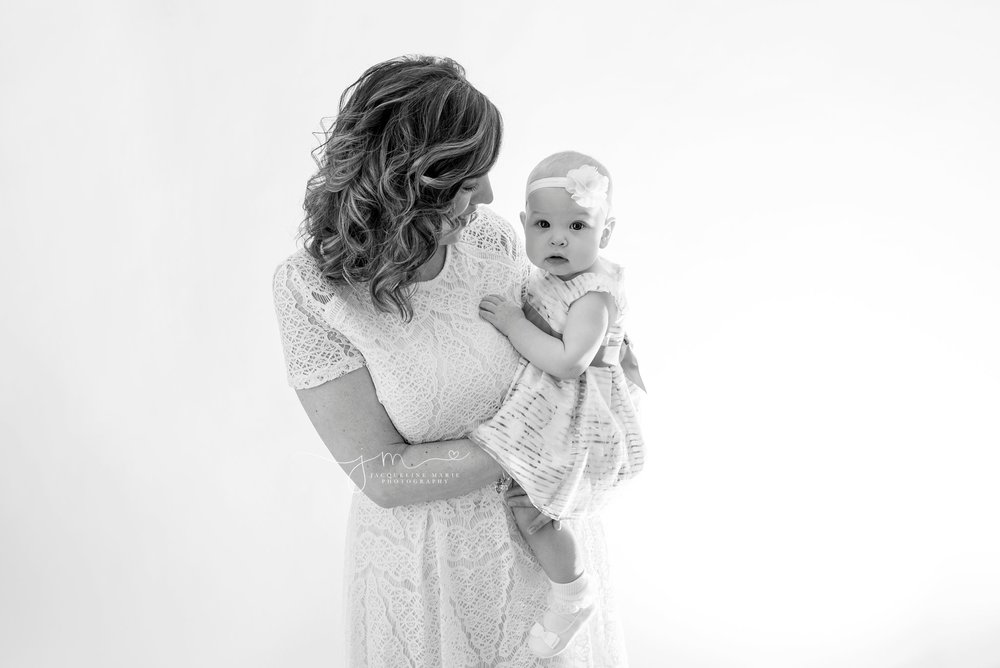 black and white image features mother holding daughter for baby photography in columbus ohio portrait studio