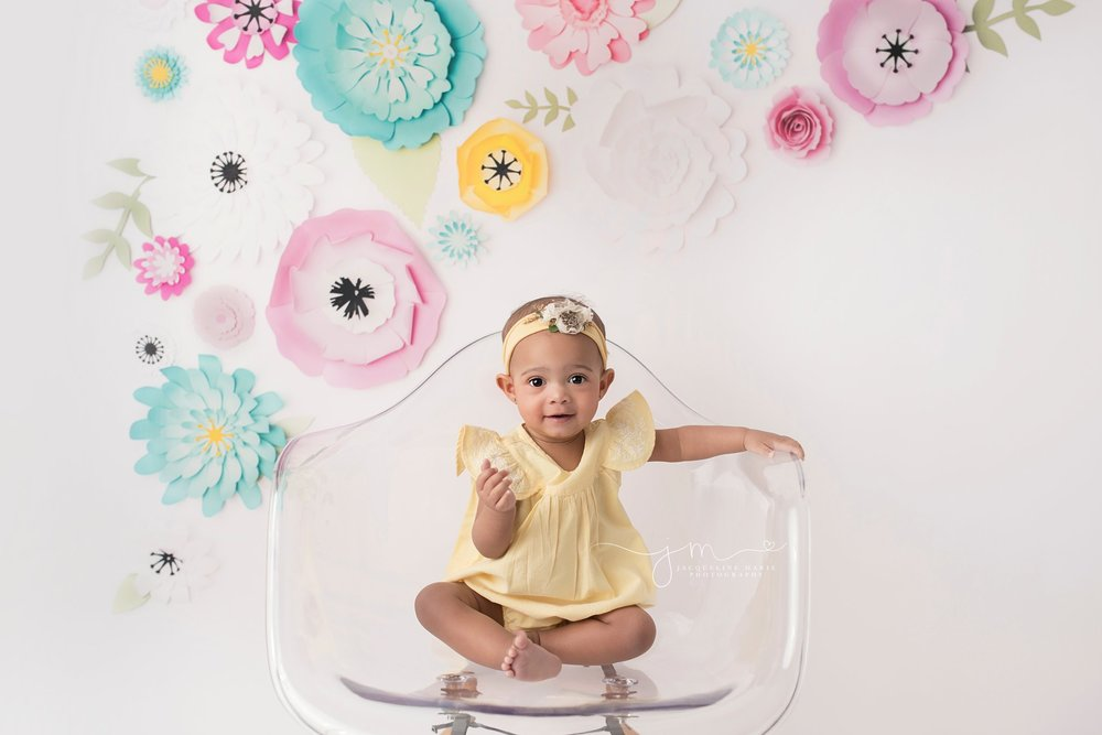 first birthday portrait features little girl wearing yellow romper and headband in Columbus ohio