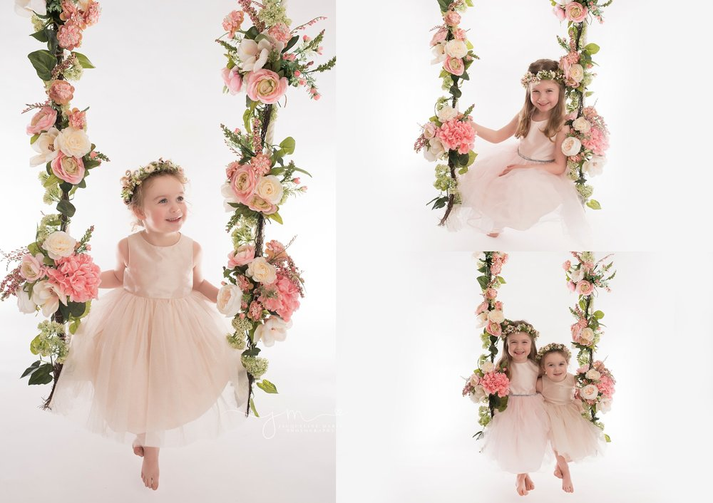 columbus ohio children and baby photographer features sisters sitting on floral swing in pink dresses