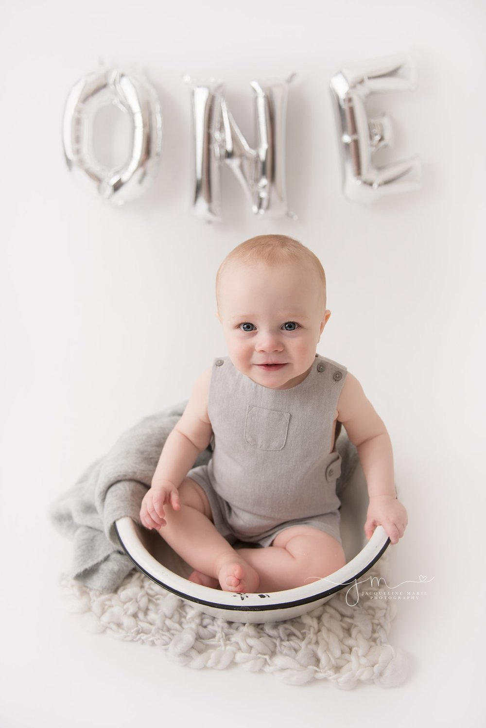 one year old baby boy wears gray romper while sitting in antique bowl for first birthday portraits in columbus ohio