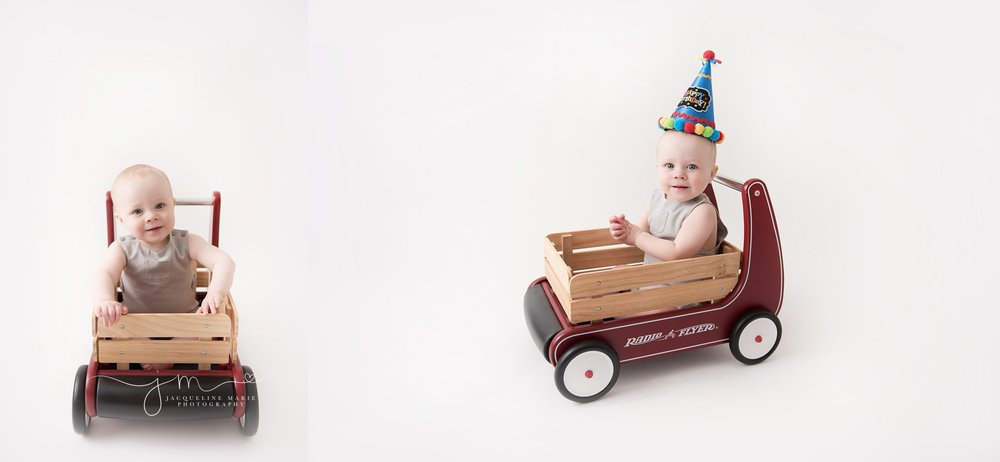 first birthday boy wears birthday hat while sitting in radio flyer wooden wagon for first birthday milestone pictures by jacqueline marie photography in columbus ohio