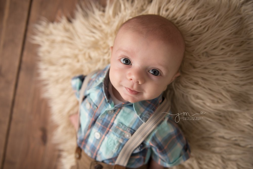 columbus ohio newborn photographer features image of 3 month old baby boy wearing plaid shirt and suspenders