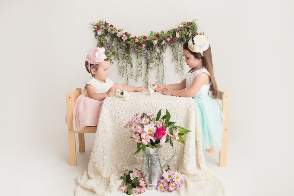 columbus ohio children photographer features sisters having a vintage tea party wearing dresses and hats at jacqueline marie photography studio