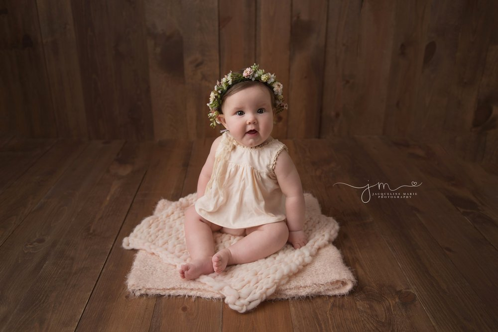 columbus ohio 6 month old baby girl sits on wood floor and wears floral crown for milestone baby pictures at jacqueline marie photography studio