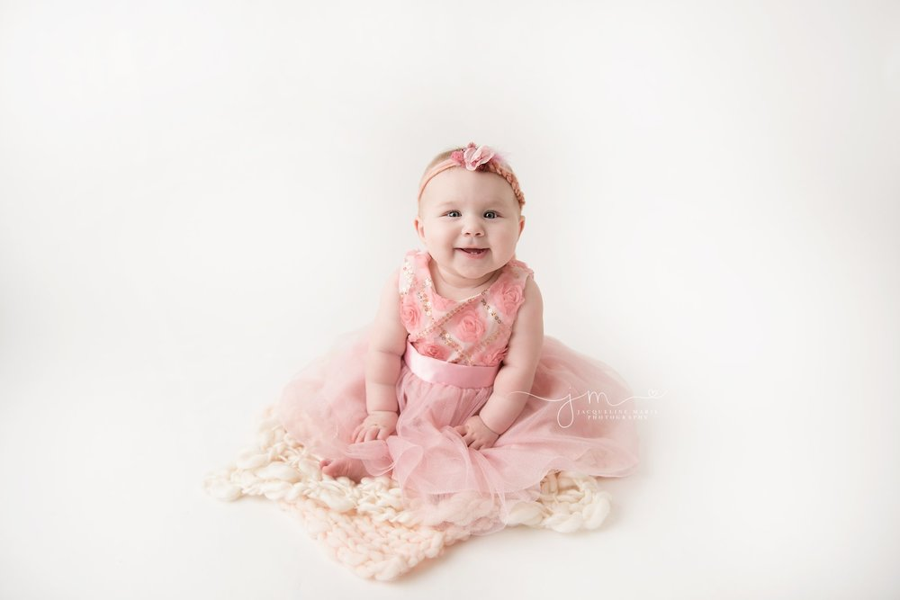 6 month old baby girl wears pink dress her grandmother got her while smiling at jacqueline marie photography studio in columbus ohio