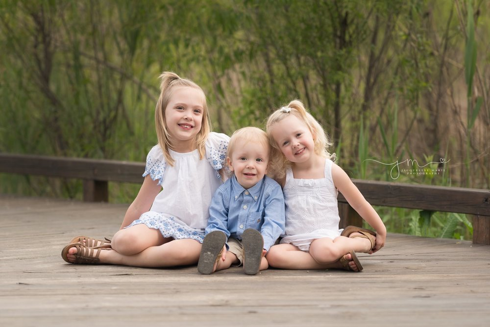 columbus ohio family and children photographer features image of brother and older sisters sitting on wood bridge at a park