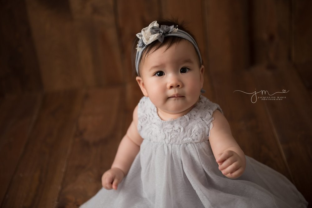 columbus ohio milestone baby photographer features baby girl in gray dress and matching headband for baby pictures
