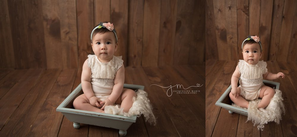 9 month old baby girl wears cream romper and blue and pink headband and sits in blue wooden bowl for milestone baby pictures in columbus ohio