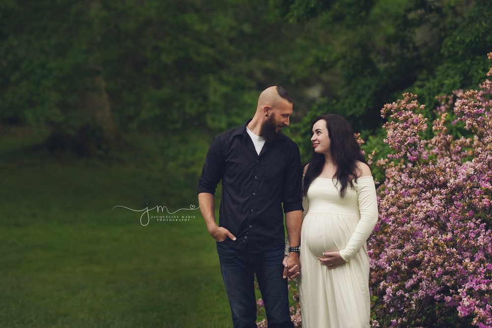columbus ohio mother and father smile next to purple flowers for maternity photography portraits