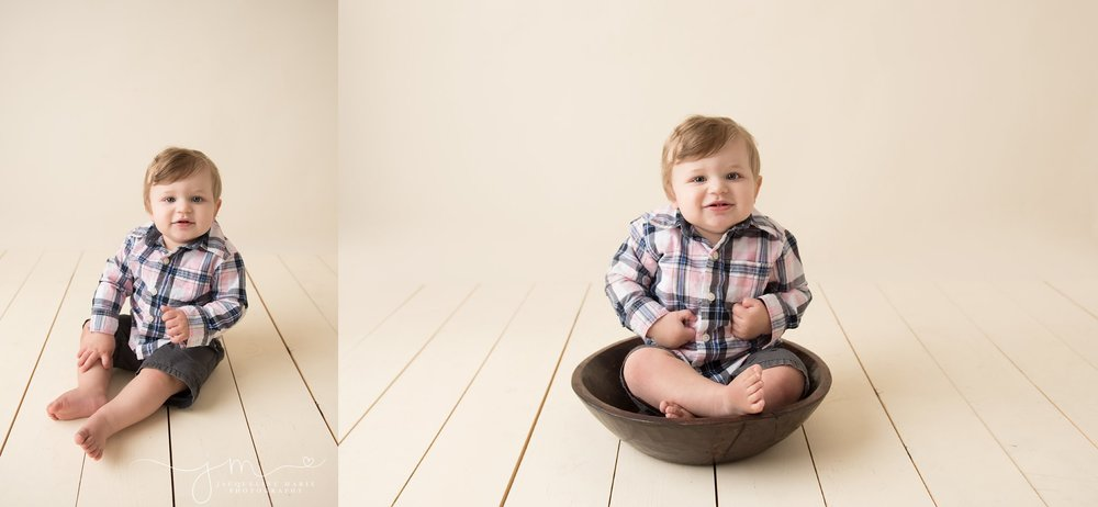 one year old baby boy wears plaid shirt while sitting in wood bowl for first birthday milestone portraits in columbus ohio