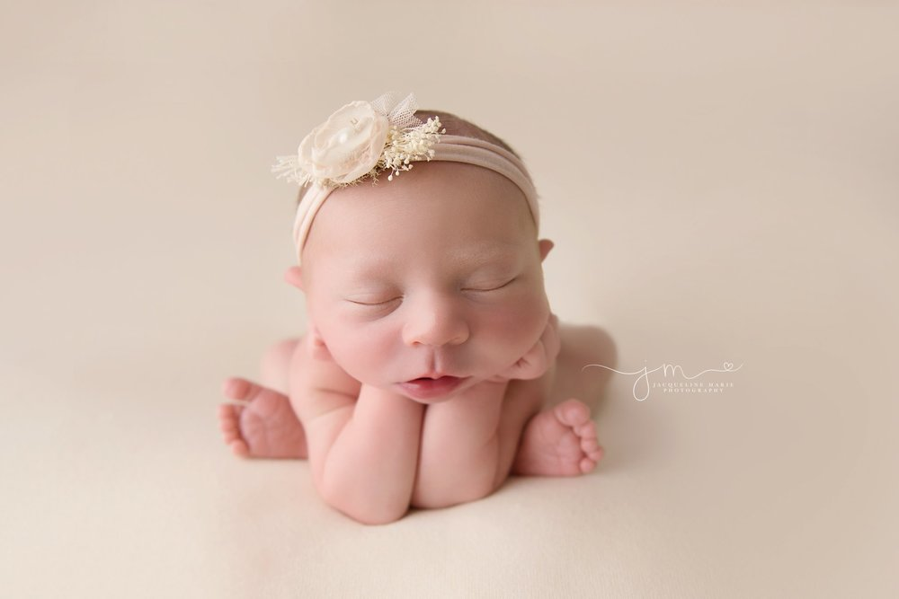columbus ohio newborn photographer features baby girl with hands on chin for newborn photography pose at portrait studio