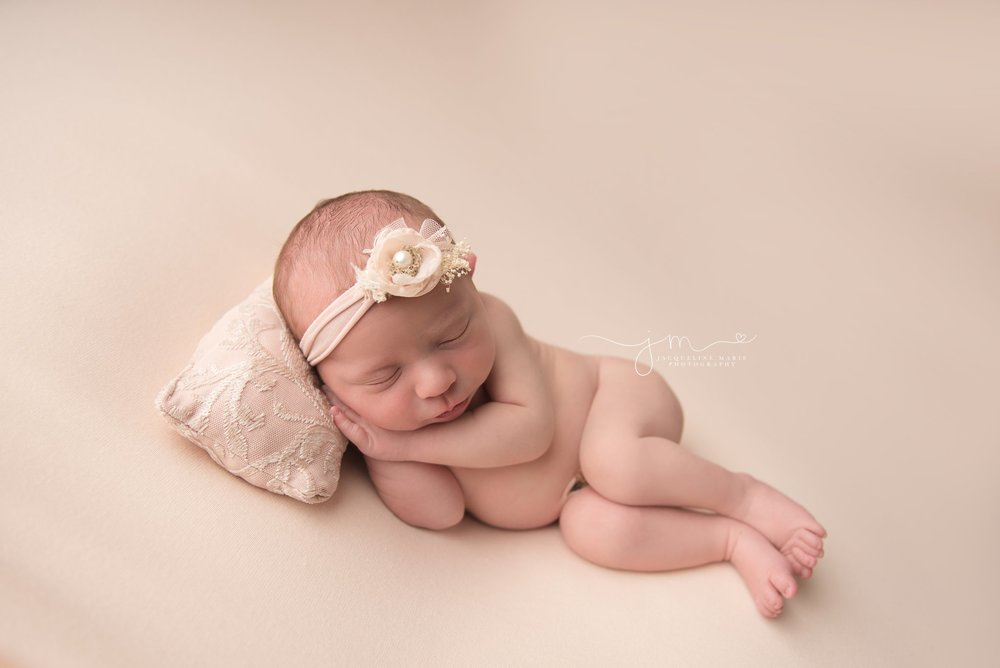 columbus ohio newborn photographer features baby girl sleeping on beaded pillow and wearing pink headband with a pearl