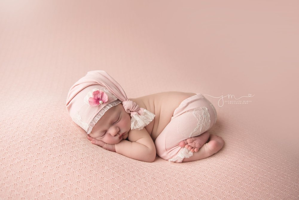 columbus ohio newborn baby girl wears pink hat with lace and flower for newborn photography portraits