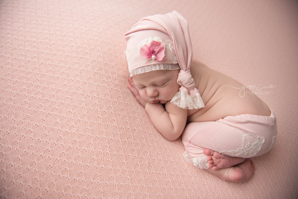 1 week old newborn baby girl wears matching pants and pink hat for newborn photography pictures in columbus ohio