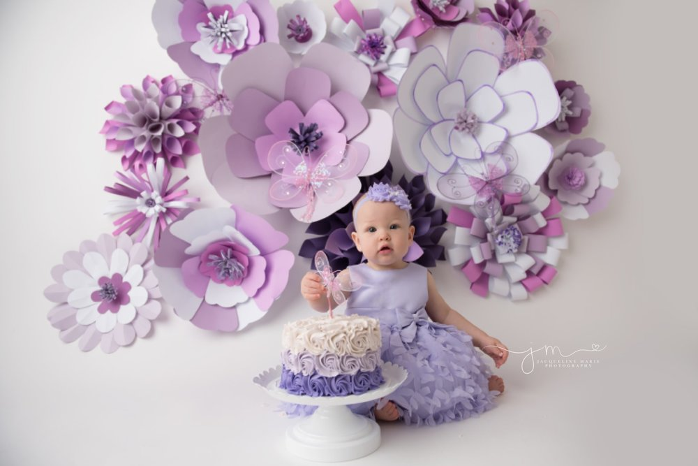 1 year old adalyn wears purple dress and matching headband for purple paper flower cake smash pictures in columbus ohio