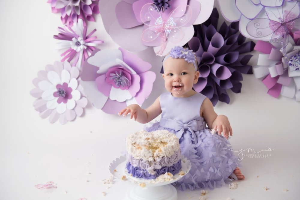 first birthday cake smash session with purple paper flowers in columbus ohio