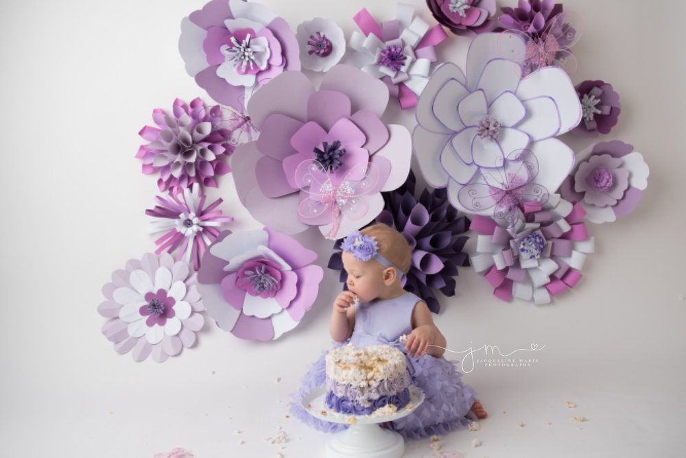 first birthday cake smash photography features purple flower cake in columbus ohio