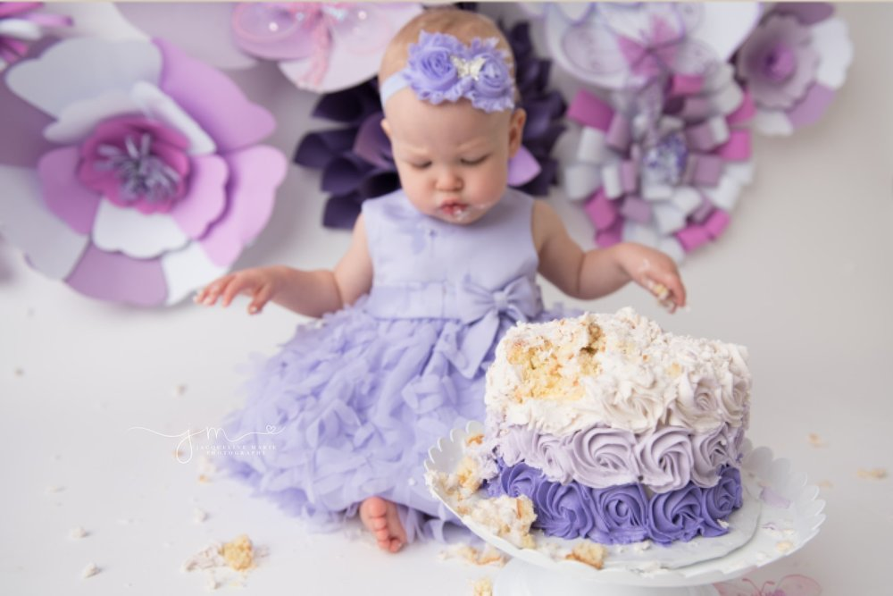 1 year old Adalyn crumbles and eats cake while wearing purple headband and matching dress for her first birthday milestone cake smash pictures in columbus ohio
