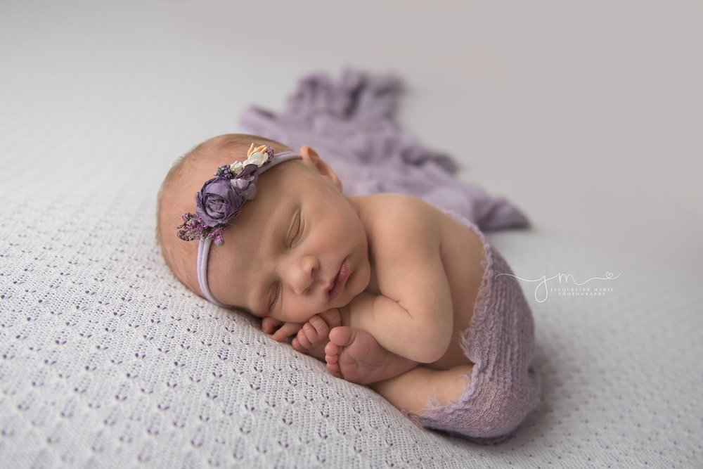columbus ohio newborn baby girl is wrapped in purple wrap and flower headband for newborn pictures by jacqueline marie photography