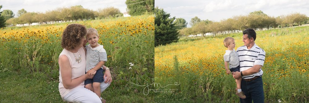 grandmother and grandfather hold their grandson and smile while telling a story at sunset in a field of flowers in columbus ohio for family photography portraits