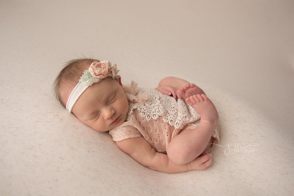 columbus ohio newborn photographer poses baby girl in peach and cream lace romper while sleeping