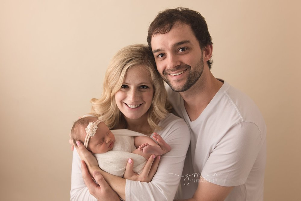 mother and father hold newborn baby girl girl at jacqueline marie photography studio in Columbus ohio for newborn photography pictures