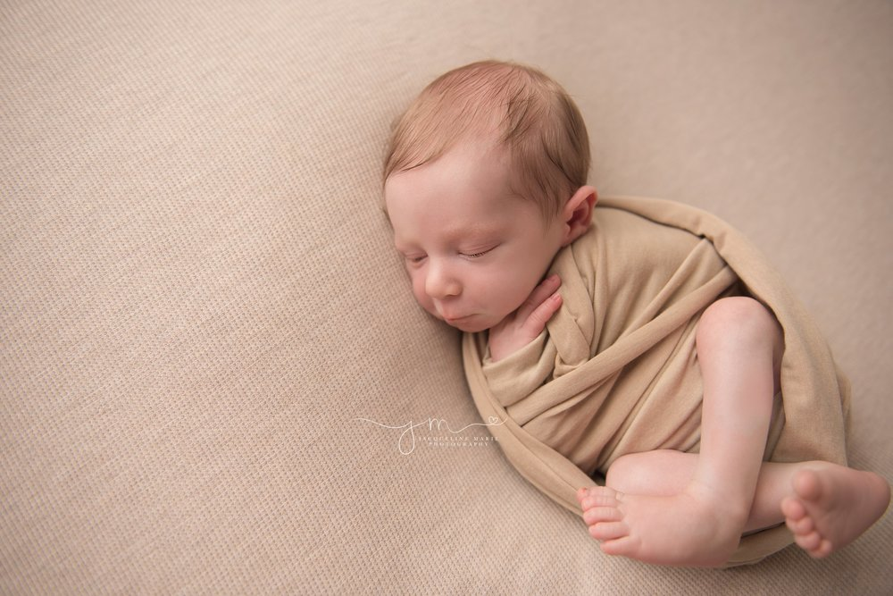 columbus ohio newborn photographer features baby boy wrapped in tan swaddle wrap while sleeping