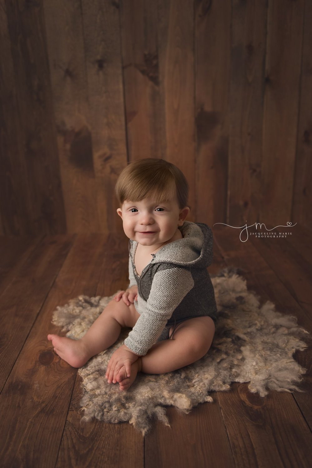 6 month old Duncan smiles on wood floor for baby milestone pictures in columbus ohio