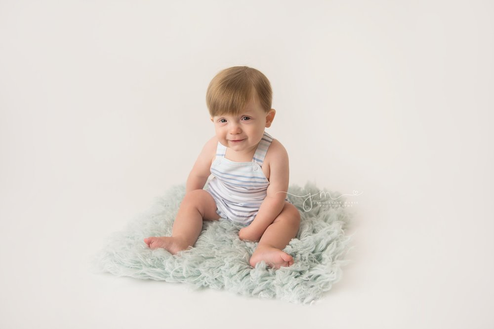 columbus ohio baby boy wears striped romper for milestone photography pictures