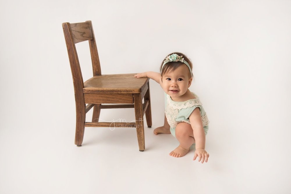 baby girl wears mint and cream romper and stands next to wood chair for first birthday milestone pictures in columbus ohio