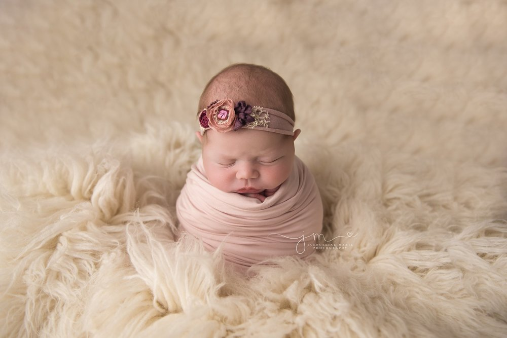 columbus ohio newborn baby girl wars pink and purple headband and is swaddled in lilac wrap for newborn photography pictures