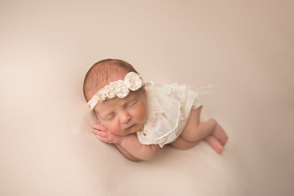 1 week old baby girl sleeps with her hands folded and wears cream floral headband in columbus ohio