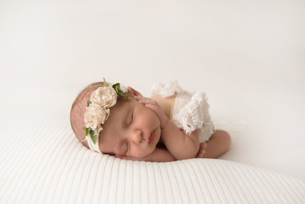 baby ella wears cream lace romper and matching headband for newborn photography session in columbus ohio