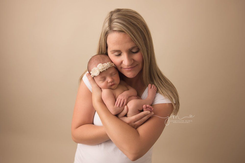 columbus ohio newborn photographer features image of mother holding newborn baby girl and smiling